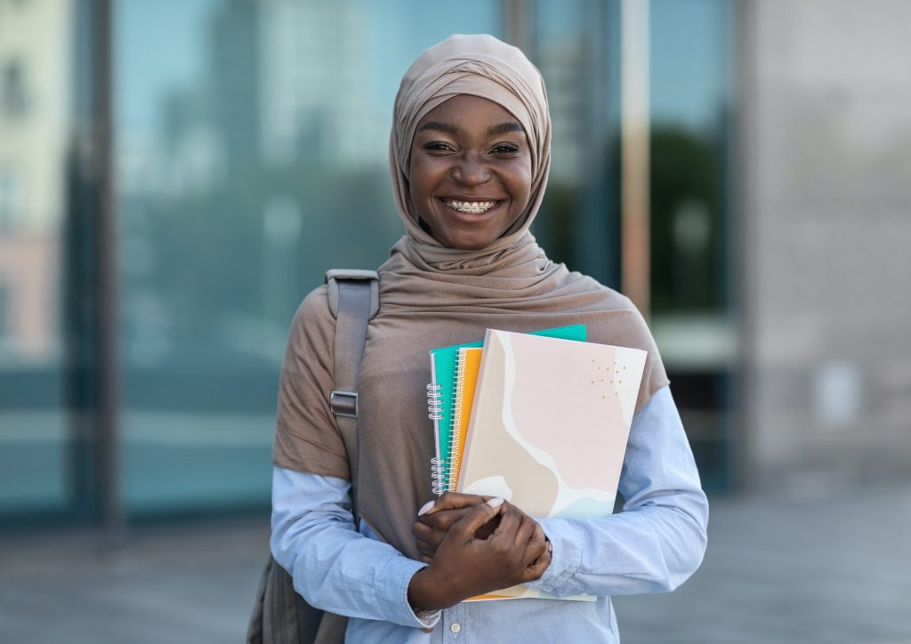 Education For Muslim Women. Smiling african islamic female college student posing outdoor